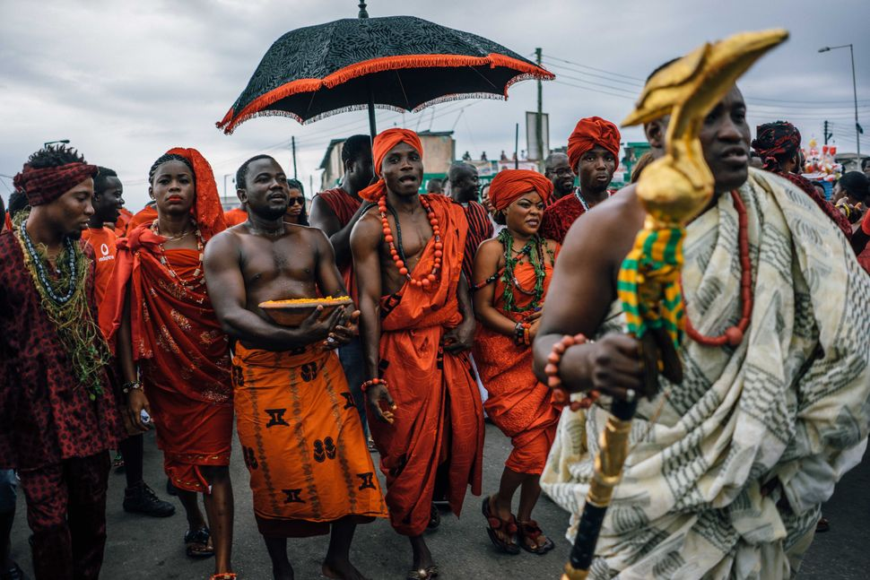 Tribal chiefs in Ghana traditionally have an entourage that, among other things, uses an umbrella to shield the chief from the sun. Here, a chief of the Ga tribe visits the Chale Wote Street Art Festival in Accra in 2015. Below, Chief Nana Munko Eku VIII of the Fante tribe visits a wedding in Cape Coast in 2020, where he and his entourage wear masks. Above: Aug. 23, 2015| Below: Aug. 8, 2020