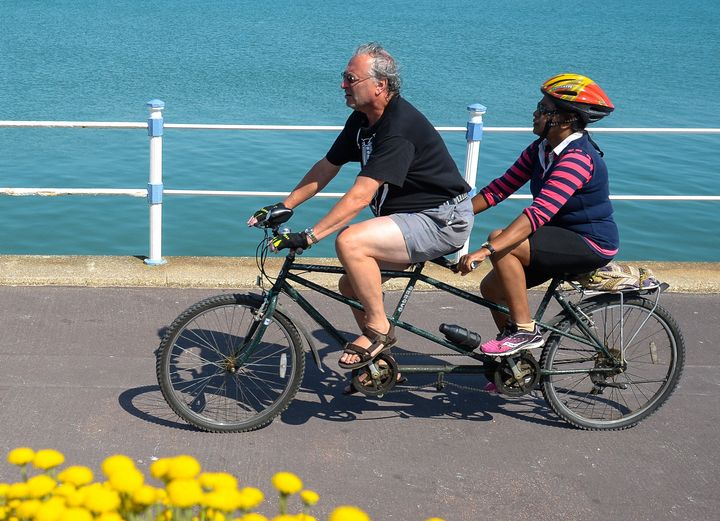 Tandem bike riders cycle along the seafront on June 24 in Weymouth, United Kingdom. Here, the tandem bike frame is clearly lo