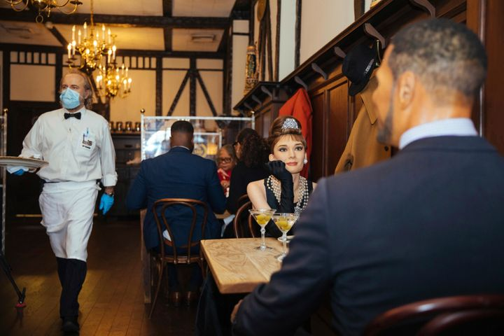 Wax statues of Audrey Hepburn and Michael Strahan occupy one of the tables at Peter Luger Steakhouse.