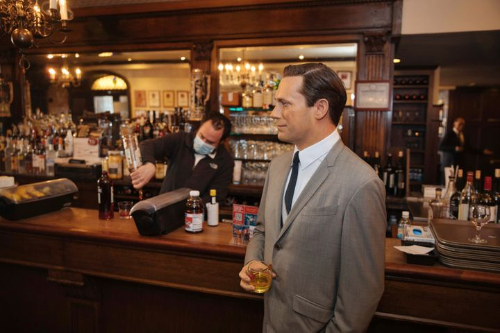 A wax statue of actor John Hamm stands by the bar with a drink at Peter Luger Steakhouse on Friday, Feb, 26, 2021, in New Yor